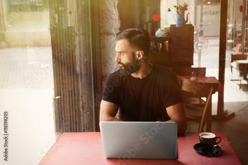 17b6da7a0af Young Bearded Businessman Wearing Black Tshirt Working Laptop Urban Cafe.Man  Sitting Wood Table Cup Coffee Looking Through Window.