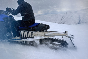 caterpillar of  snowmobile rides in the mountains, rear view