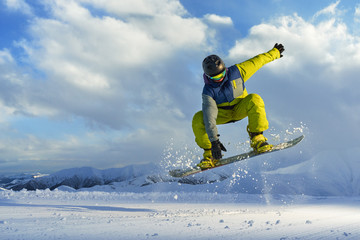 snowboarder does the jumping trick. snow scatters pieces