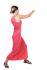 skinny woman funny fights waving his arms and legs. Isolated over white background. A slender woman in a long red dress punches.