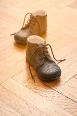 Baby boots on wooden vintage floor. First steps. Childhood