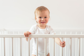 Portrait of a laughing baby standing in a crib and looking at the camera.