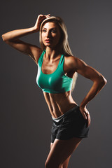 Handsome fitnes woman.Very power athletic girl posing on a colorful background.l Shallow depth of field