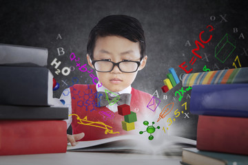 Little boy learns with books and formula