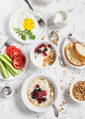 Table breakfast - cottage cheese with yogurt and berries, oatmeal with honey and berries, fried egg, fresh vegetables,  homemade granola on a light background. Healthy food. Top view