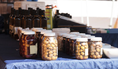 Jars of colorful olives grown and pickled in Southern California and displayed at a farmers market.