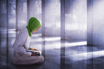 Young asian muslim woman reading the koran