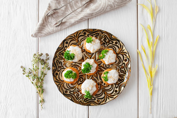 Tasty tartlets with cheese cream and parsley, flat lay. Top view on plate with stuffed crackers on white wooden background, served with herbs and serving tongs on napkin