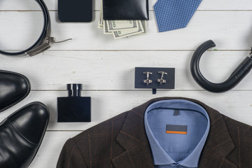 set of men's clothing and shoes on wooden background.