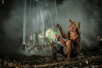 The old fisherman was preparing nets for fishing.Thailand