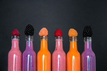 Six bottles with smoothies and raspberry, (red, yellow, blackberry) on black background. Milk shake in glass jar with berries. diet or vegan food concept, fresh vitamin.