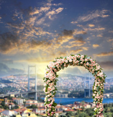 wedding arch decorated with flowers of roses with Bridge over Bosphorus at sunset on the background. Wedding and honeymoon concept