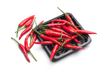 Heap of red hot chili pepper in black container on white backgro