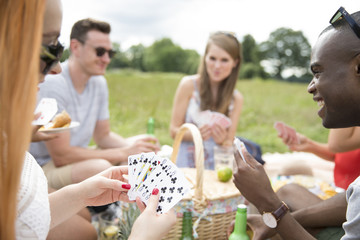Group Of Friends Playing Card Game During Picnic
