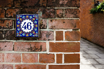 Hand-painted decorative house number tile on a brick wall – 46 (forty-six)