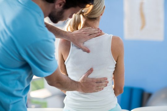 Male physiotherapist giving back massage to female patient