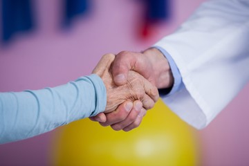Physiotherapist shaking hands with patient
