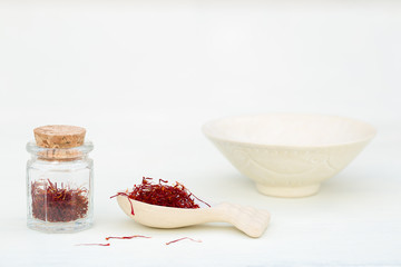 Saffron pistil in spoon and in glass jar on white background