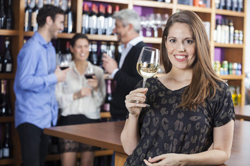 Woman Holding Wineglass While Friends Standing In Background