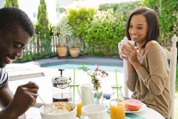 Young couple enjoying breakfast in garden