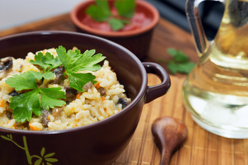 Rice with mushrooms and carrot or pilaf on wooden rustic table