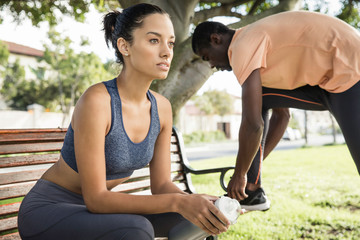 Woman wearing spandex sitting on park bench looking away