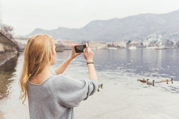 Young woman photographing from lakeside, Lake Como, Italy