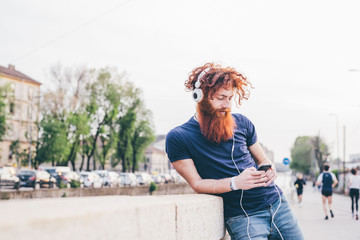 Young male hipster with red hair and beard choosing headphone music in city