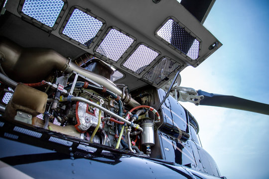 Close up of motor of black with gray stripes bell 407 helicopter standing on green grass field on blue sky background.