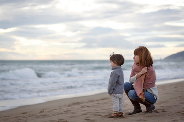 Mother and daughter on beach looking at ocean