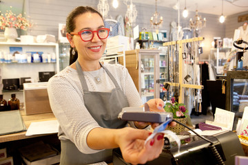 Female sales assistant taking credit card payment at checkout in gift shop