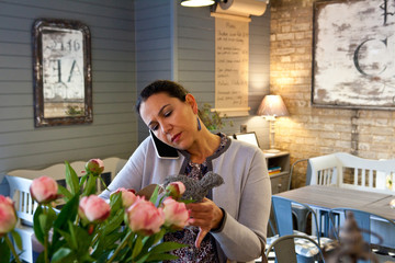 Mature female customer reading menu whilst talking on smartphone in cafe