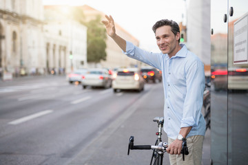Mature male cyclist waving from city street
