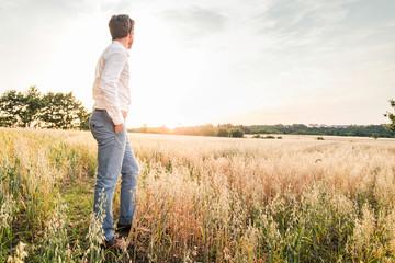 Smart young man looking across field, Kirchheimbolanden, Rheinland-Pfalz, Germany