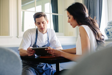 Young male chef planning menu with female manager using digital tablet