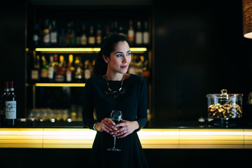 Young woman with glass of wine standing in bar