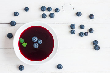 Blueberry soup on wooden white background. Top view, flat lay