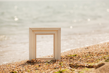 Photo frame on sand beach