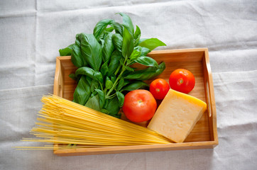 Green basil, chunk of parmesan cheese, raw cappellini and tomatoes
