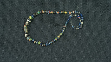 Variety of ancient glass beads in necklace on black silk fabric  background