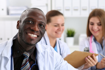 Portrait of young handsome black male doctor with colleagues