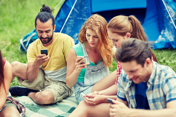 friends with smartphone and tent at camping