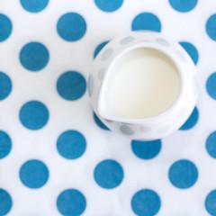 Milk jug on white ceramics on polka dot background