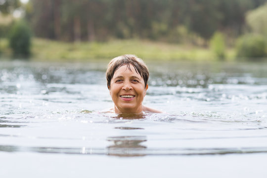 Healthy senior woman swimming in the lake or river. Happy elderly lady enjoying active summer vacation. Sportive lifestyle. Active retirement concept.