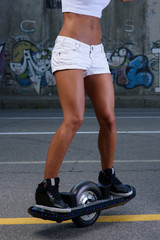 sporty athletic caucasian cute teen riding electric onewheel skateboard having fun in the street posing and hold in her hands