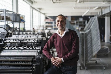 Smiling mature man in a printing shop