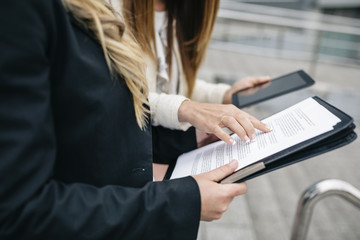 Two businesswomen with digital tablet and documents outdoors
