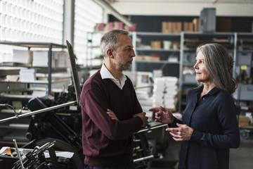 Senior woman and man talking in a printing shop