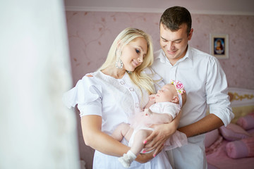Pretty mother holds her newborn baby on the arms while posing wi