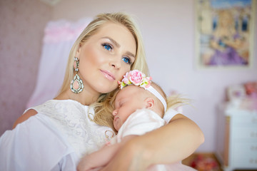Blue-eyed woman looks far away while holding tiny child in her a